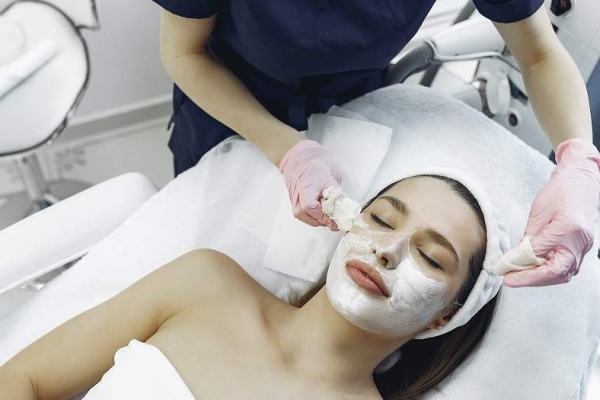 Lady having special cream applied to her face in a medical cosmetic clinic.